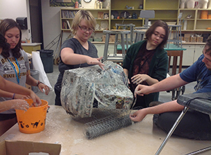 Students working on paper mache dragon